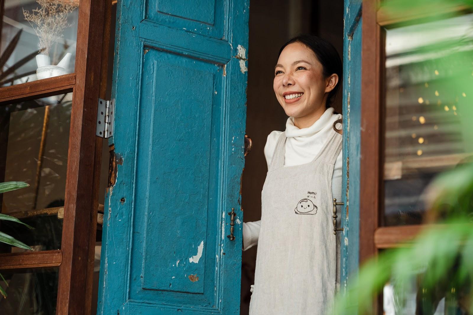 Pessoa sorrindo na janela de seu negócio